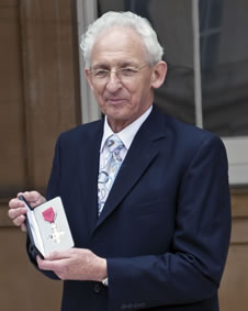Our chairman shows the MBE medal outside Buckingham Palace